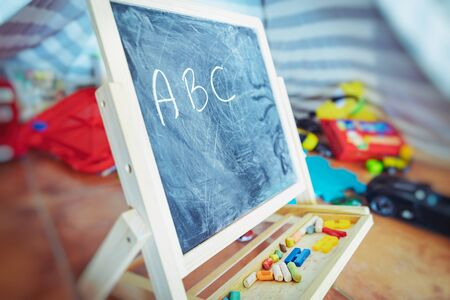 Photo pour Little chalkboard standing among different toys in a baby's room, start learning of alphabet, preschoolers education, back to school concept - image libre de droit