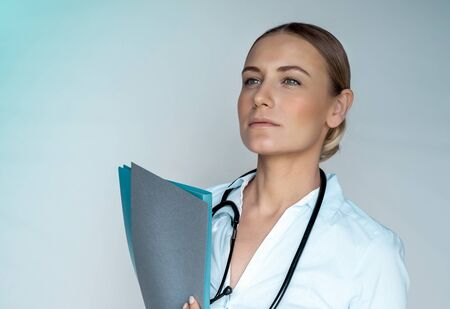 Photo for Serious concerned woman doctor with medical records in hands, isolated on gray background, thoughtfully looking away, health and medical care - Royalty Free Image
