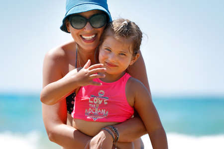 Photo for Portrait of a Beautiful Cheerful Mother Hugging her Cute Little Daughter on the Beach. Enjoying Time Together. Happy Summer Vacation. - Royalty Free Image