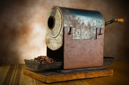 vintage roaster with coffee beans in the wood table