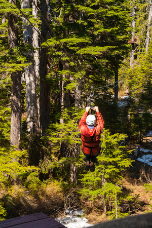 Man crossing the forest by zip line