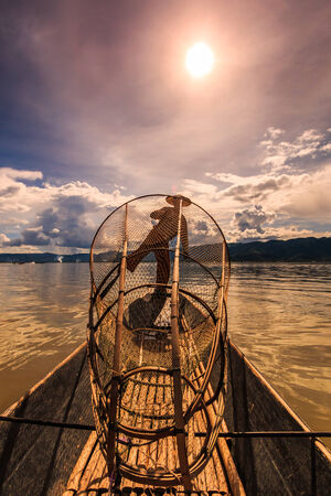 Myanmar Inle lake fisherman on boat catching fish by traditional net in village Inlay Shan state of Myanmar
