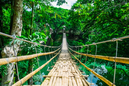 Photo pour Bamboo pedestrian suspension bridge over river in tropical forest, Bohol, Philippines - image libre de droit