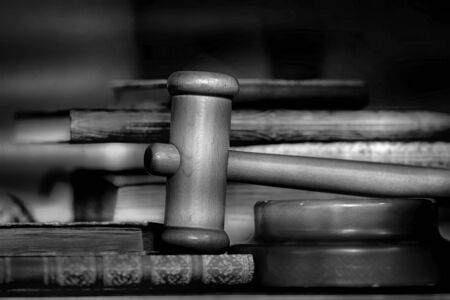 Court wooden hammer and old books on a wooden table - black and white