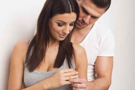 Young couple giving each other an engagement ring