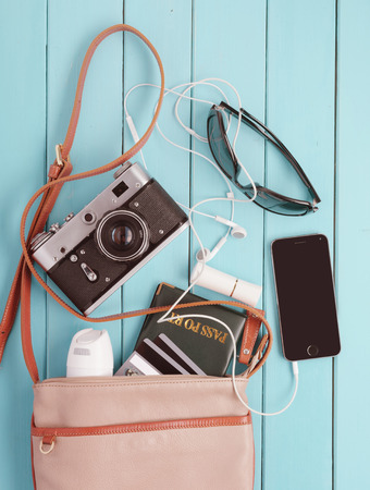 female bag with a variety of personal belongings and with retro camera. set traveler