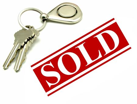Sold sign and two keys on a key ring. Real estate sale and purchase concept.