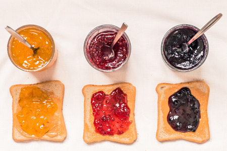 Toast sandwiches with peanut butter and jam raspberry, blueberries, orange top view