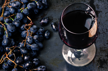 Wineglass of red wine with grapes on black background