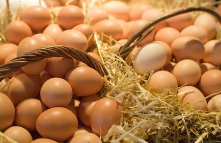 Tiled eggs in straw baskets on market stall.