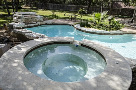 Large Upscale hot tub attached to kidney shaped swimming pool