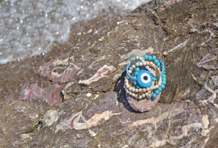 greek summer bracelets with evil eye on beach - summer jewelry advertisement