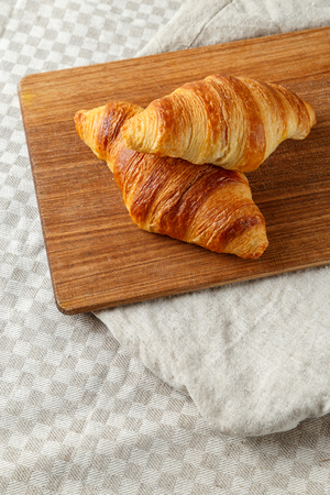 Delicious french freshly baked croissants on a wooden cutting board.