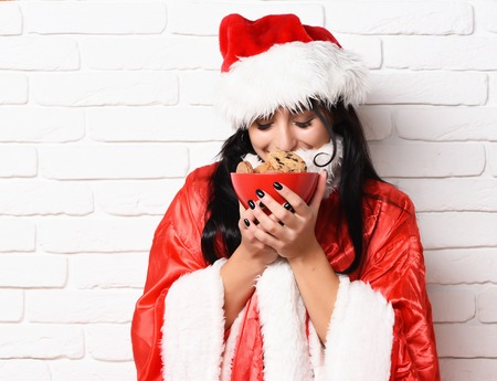 pretty cute  santa girl or smiling brunette woman in new year sweater and hat holding and sniffing christmas or xmas chocolate hip cookies in bowl on white brick wall background