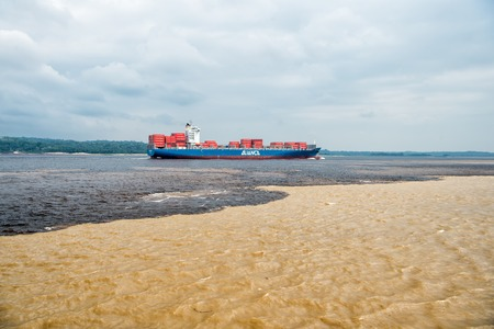 Manaus , Brazil- Decemcer 4, 2015: water meeting in Brazil -amazon river with rio del negro clean and dirty river water with different streams. Cargo ship paasing water meeting