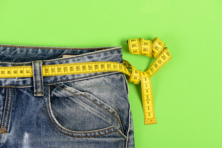 Foto de Close up of jeans with measure tape around waist. Healthy lifestyle and dieting concept. Upper part of denim trousers isolated on green background. Blue jeans with yellow measure tape instead of belt. - Imagen libre de derechos