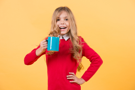 Girl with long blond hair in red sweater hold mug. Child smile with blue cup on orange background. Health and healthy drink. Thirst, dehydration concept. Tea or coffee break.