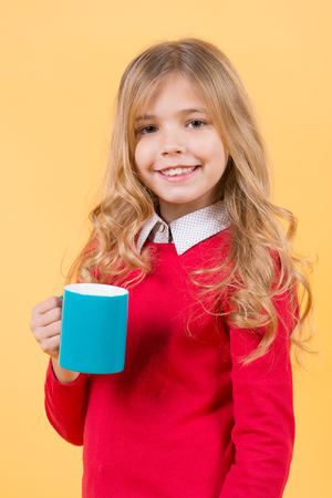 Girl with long blond hair in red sweater hold mug. Child smile with blue cup on orange background. Thirst, dehydration concept. Tea or coffee break. Health and healthy drink.