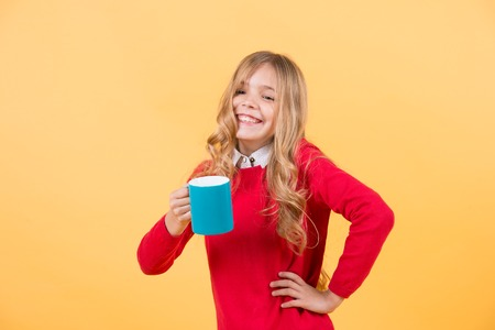 Girl with long blond hair in red sweater hold mug. Child smile with blue cup on orange background. Thirst, dehydration concept. Health and healthy drink. Tea or coffee break.
