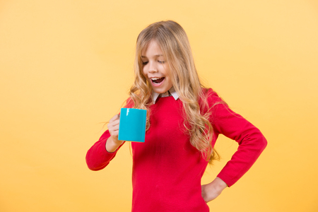 Tea or coffee break. Girl with long blond hair in red sweater hold mug. Child smile with blue cup on orange background. Thirst, dehydration concept. Health and healthy drink.