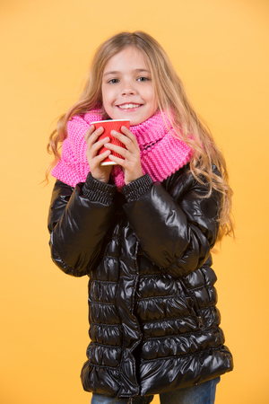 Girl with long blond hair in black jacket hold mug. Child smile with red cup on orange background. Tea or coffee take away. Warm up drink. Autumn season concept.