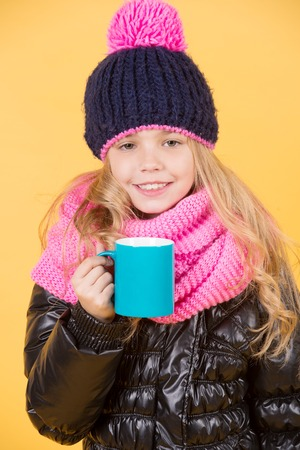 Girl in hat, pink scarf, black jacket with mug. Child with blue cup smile on orange background. Hot drink in cold weather. Tea or coffee break. Autumn season relax concept.