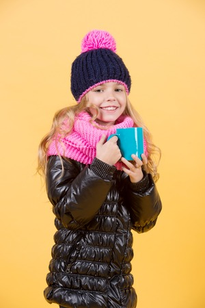 Tea or coffee break. Girl in hat, pink scarf, black jacket with mug. Child with blue cup smile on orange background. Autumn season relax concept. Hot drink in cold weather.