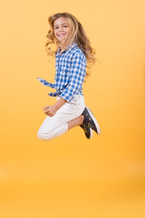Child bounce with smiling face. Girl jump on orange background. Happy childhood concept. Fashion, beauty, look. Punchy pastel trend.
