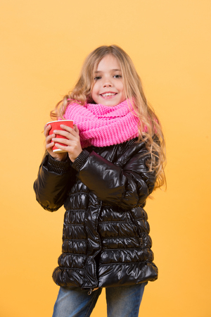 Girl with long blond hair in black jacket hold mug. Child smile with red cup on orange background. Autumn season concept. Tea or coffee take away. Warm up drink.