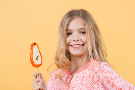 Happy childhood concept. Girl smile with lollipop on orange background. Child smiling with candy on stick. Food, dessert, snack. Punchy pastel trend