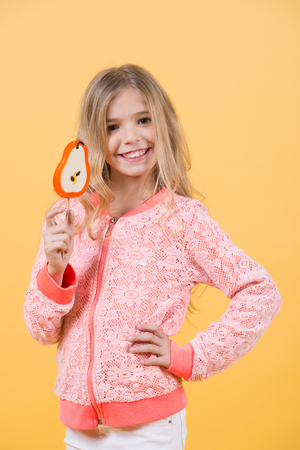 Girl smile with lollipop on orange background. Child smiling with candy on stick. Happy childhood concept. Food, dessert, snack. Punchy pastel trend