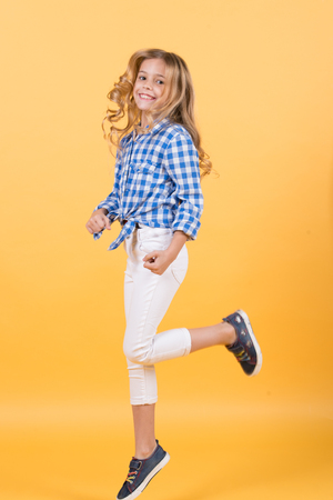 Girl jump on orange background. Child bounce with smiling face. Happy childhood concept. Fashion, beauty, look. Punchy pastel trend.