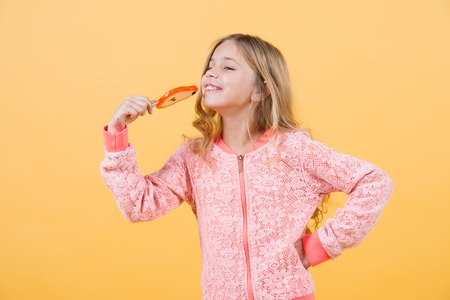 Candy girl pose on orange background. Candy on stick at childs face.