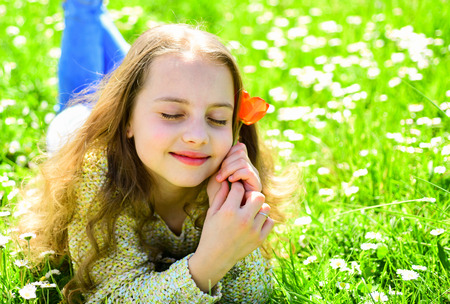 Girl lying on grass, grassplot on background. Girl on dreamy face holds red tulip flower, enjoy aroma. Child enjoy spring sunny day while lying at meadow with flowers. Seasonal allergy concept