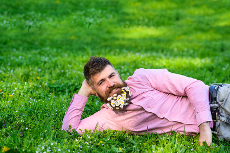 Man with beard on smiling face enjoy nature. Masculinity concept. Hipster with daisies in beard looks attractive. Bearded man with daisy flowers lay on meadow, lean on hand, grass background