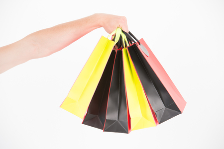 Male hand holds five shopping bags. Shopping concept. Hand holds bunch of colorful shopping bags. Shopping on black friday. Client bought lot items with discount
