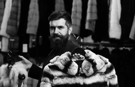 winter sale. Guy with beard chooses furry coats. Shop assistant with expensive overcoats. Elegance and glamour concept. Man with happy face holds furry coats with clothes rack on background