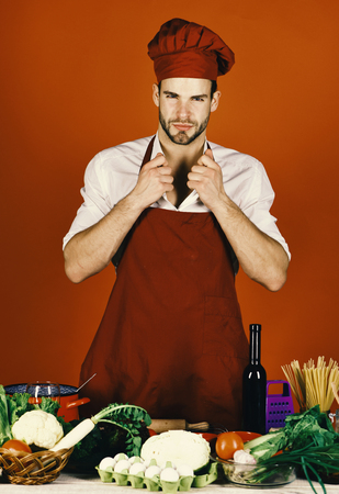 Chef with sexy face poses in uniform on red background. Cuisine and professional cooking concept. Man in cook hat and apron adjusts collar. Cook works in kitchen near table with vegetables and tools.