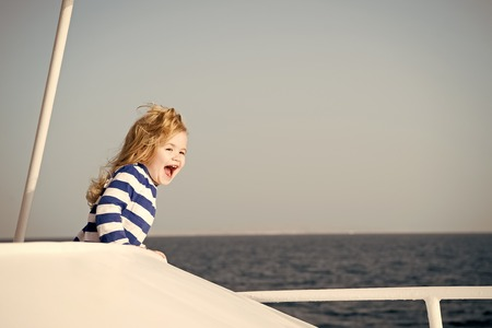 small baby boy sailor or happy child captain of yacht, boat with blonde hair and smiling face in stripped marine shirt sunny outdoor on natural background, blue sky and water. traveling, childhood