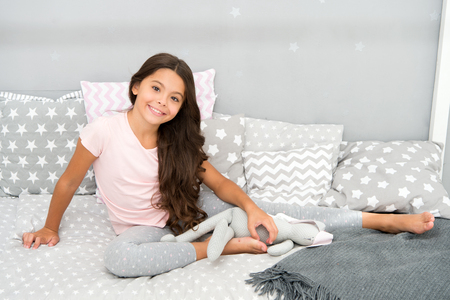 Foto per Enjoying happy childhood. Happy small girl. Small girl relax on bed. I have a pretty idyllic childhood. - Immagine Royalty Free