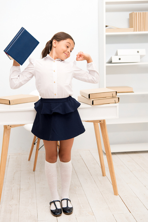 Foto de Girl child hold book while stretching white interior. Kid school uniform making exercise stretching increase productivity. Exercises to maintain vivacity. Role of active breaks in educational process. - Imagen libre de derechos