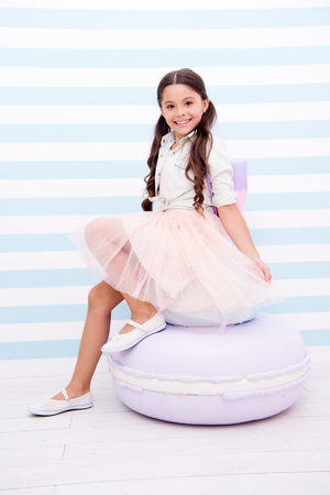Photo pour Sweet princess. Child girl adorable smiling face posing on cute sweet macaroon pouf. Kid long curly hair wear fashionable outfit. Girl with cute bag posing striped background. She likes to be model. - image libre de droit