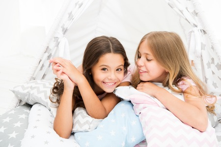 Photo pour Sisters share gossips having fun at home. Pajamas party for kids. Cozy place tipi house. Sisters or best friends spend time together lay in tipi house. Girls having fun tipi house. Girlish leisure. - image libre de droit