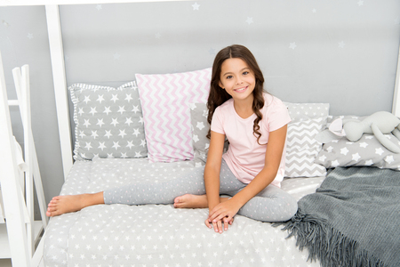 Foto de Cute and adorable. Little girl relax on bed. Happy little girl. Childhood years. One of the luckiest things is to have a happy childhood. - Imagen libre de derechos
