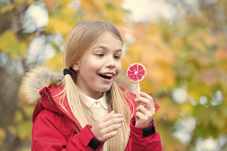 Food, dessert, snack. Child smiling with candy on stick outdoor. Girl smile with lollipop on natural background. Happy childhood concept. Punchy pastel trend
