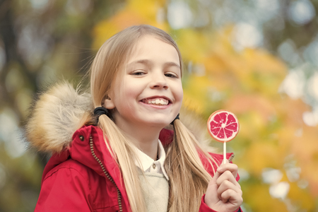 Girl smile with lollipop on natural background. Child smiling with candy on stick outdoor. Happy childhood concept. Food, dessert, snack. Punchy pastel trend