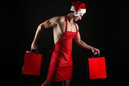 Foto de Sexy athletic macho muscular chest in santa claus hat. Athlete muscular man wear santa hat and apron. I have gift for you. Macho muscular torso posing with shopping bags. Santa claus for adult. - Imagen libre de derechos