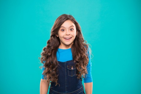 Kid girl long healthy shiny hair wear casual clothes. Little girl excited happy face. Kid happy cute face feels excited blue background. Sincere excitement. Exciting moments. Excitement emotion.