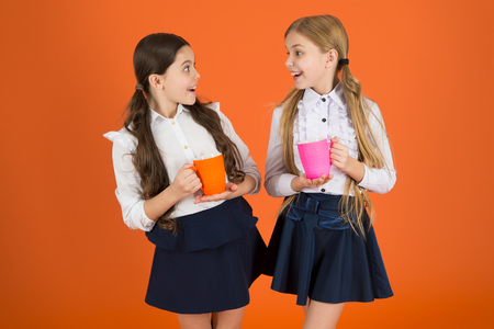 Foto de Tea break. Girls kids school uniform orange background. Schoolgirl hold mug. School lunch. Having break relax. Drinking tea while break. School mates relaxing with drink. Hydration and water regime. - Imagen libre de derechos