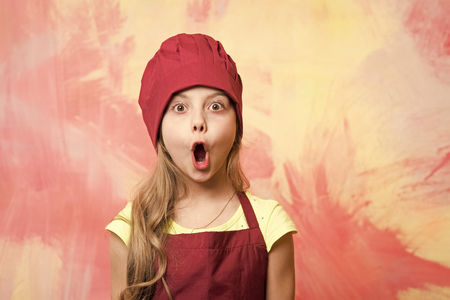 Photo pour Girl cook with open mouth and surprised face. Child and happy childhood. Career, uniform, dream, occupation and profession concept. Kid in chef hat and apron on colorful wall. Cooking and playing. - image libre de droit